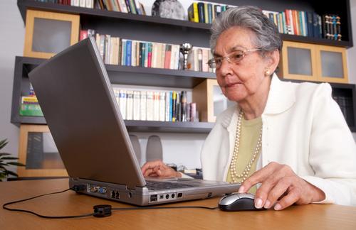 señora mayor sentada frente a una computadora mirando la pantalla