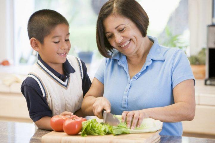 señora cortando vegetales con su nieto menor de edad ambos sonrien