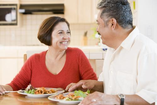 mujer y hombre, adultos mayores sentados mirándose y con platos de comida
