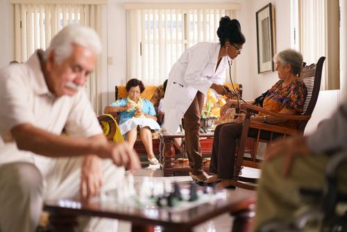 personas mayores en una sala realizando diferentes actividades acompañados de una doctora