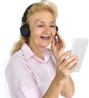mujer mayor sonriendo con audífonos y sosteniendo un celular
