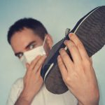 hombre sosteniendo zapato con mal olor, mientras se tapa la nariz