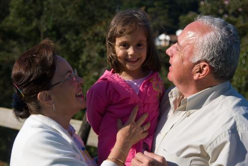 mujer y hombre adultos mayores cargando entre los dos a una niña pequeña