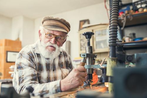 hombre adulto mayor con barba blanca sosteniendo un aparato de trabajo