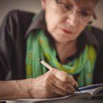 mujer adulta mayor sosteniendo un boligrafo mientras escribe