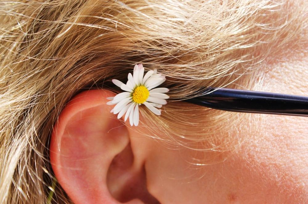 oreja de mujer de cabello rubio con flor y parte de armazon de lentes