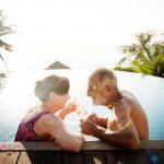 pareja de adultos mayores en una piscina con vista al mar y palmeras al atardecer