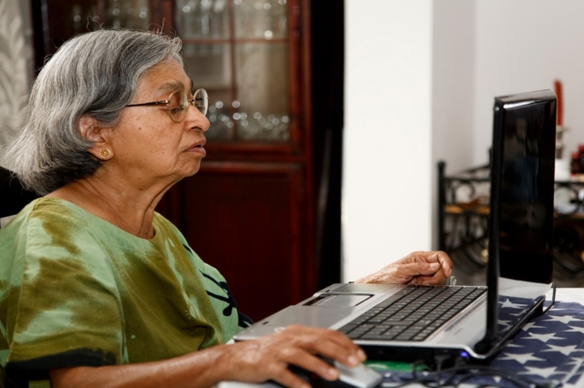 mujer canosa y de lentes con blusa verde frente a computadora