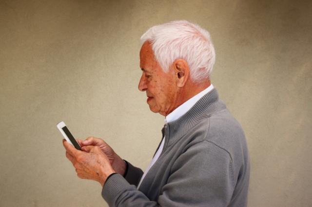 adulto mayor con camisa blanca y sueter gris con manos en su celular