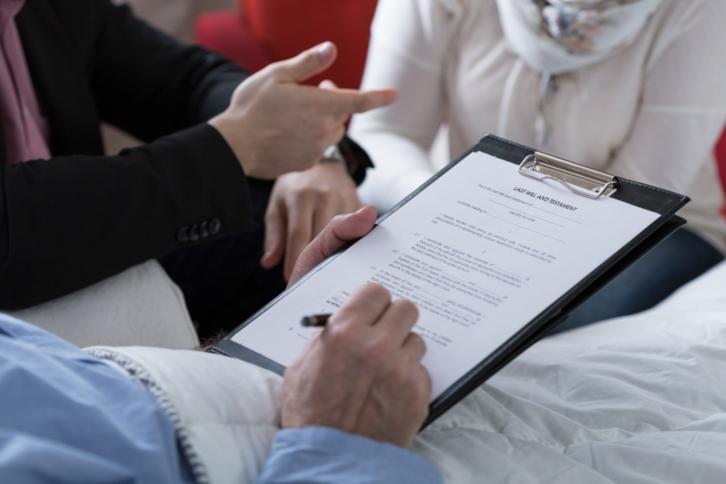 tres personas una recostada en cama firmando su testamento