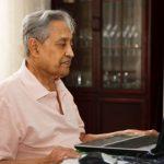 adulto mayor con camisa color melon frente a una laptop