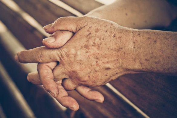 par de manos de adulto recargadas en madera con manchas seniles