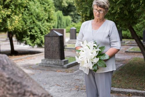 señora en duelo por la perdida de su ser querido llevando flores al cementerio