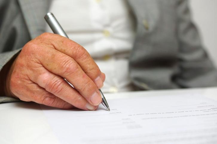 hombre mayor sosteniendo una pluma escribiendo sobre hoja de papel