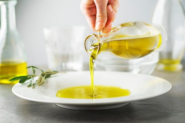 mesa con una persona sirviendo aceite de oliva en plato blanco