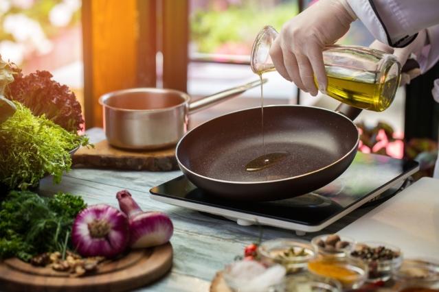 persona vertiendo aceite de oliva sobre sarten en una cocina
