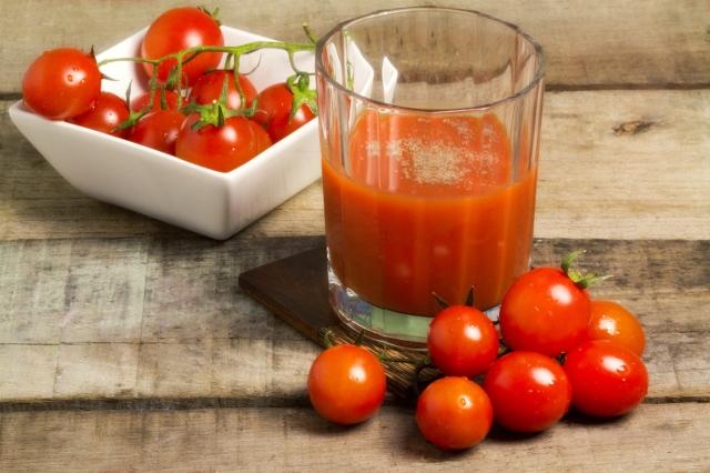 mesa con plato de tomates y un vaso con jugo de tomates