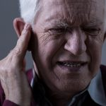 persona de la tercera edad tocándose el oído con señales de dolor