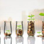 persona recopilando monedas en vasos transparentes
