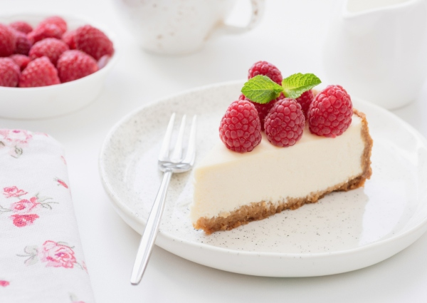 rebanada de cheesecake de moras sobre plato blanco y tenedor