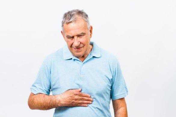 persona adulto mayor de camisa azul cielo con aparente dolor en el estomago