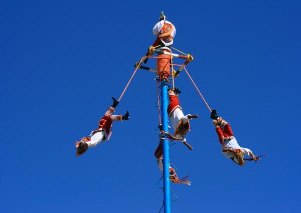 cinvo hombres colgados de un poste azul llamados voladores de papantla