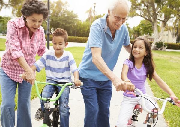 par de abuelos con su par de nietos montados en bicicleta celebrando el dia del abuelo
