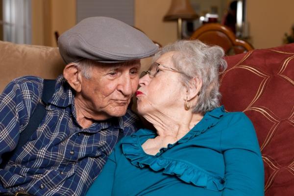 par de adultos mayores sentados ella dandole un beso a el mes del adulto mayor