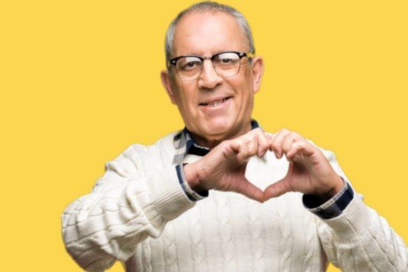 persona adulto mayor de lentes sueter balnco formando un corazon con las manos