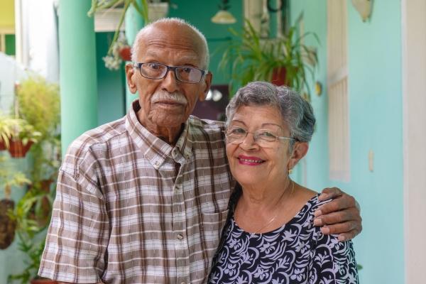pareja de adultos mayores abrazados al fondo su casa