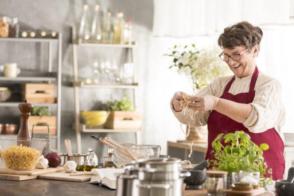persona de la tercera edad cocinando en casa con una gran sonrisa