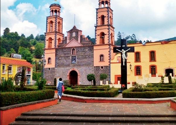 iglesia cruz y parque con arbustos y una persona caminado