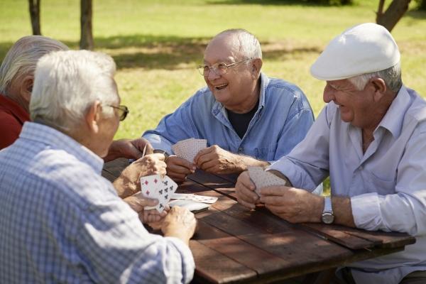cuatro adultos mayores al rededor de una mesa jugando cartas