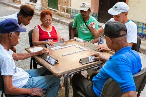 varias personas al rededor de una mesa jugando domino