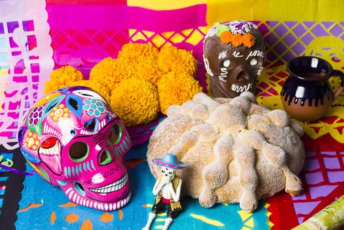 Pequeña ofrenda de muertos con calaveritas de chocolate, papel picado, flores, pan de muerto y calaverita de madera
