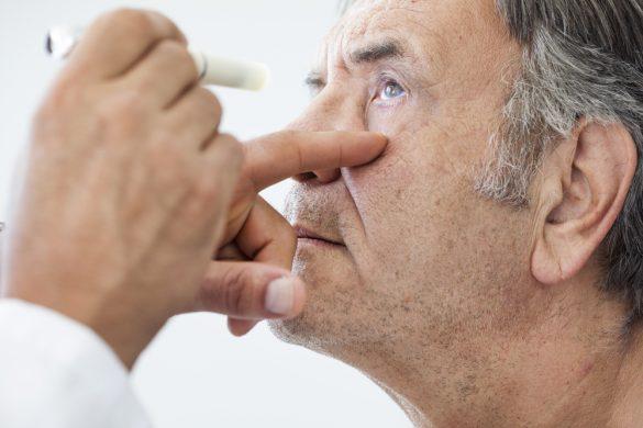 persona de la tercera edad siendo revisada por un optometrista