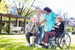 grupo de adultos mayores en jardín con una enfermera